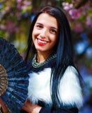 有花魅力白色毛皮和黑爱好者的美丽的妇女在手中 图库摄影