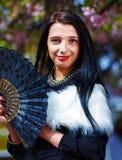 有花魅力白色毛皮和黑爱好者的美丽的妇女在手中 免版税图库摄影