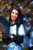 有花魅力白色毛皮和黑爱好者的美丽的妇女在手中 库存图片