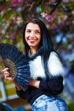有花魅力白色毛皮和黑爱好者的美丽的妇女在手中 免版税库存照片