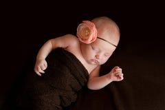 有花头饰带的新出生的女婴 免版税图库摄影