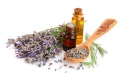 有芳香在白色背景隔绝的油和淡紫色花的瓶 免版税库存图片