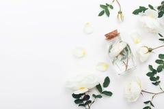 有芳香水和白色玫瑰的玻璃瓶子为温泉和芳香疗法开花 顶视图和平的位置样式 免版税库存图片
