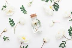 有芳香水和美丽的玫瑰色花的玻璃瓶子温泉和芳香疗法的 顶视图和平的位置样式 库存图片