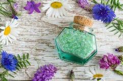 有芳香腌制槽用食盐的小玻璃瓶子与花萃取物 库存照片