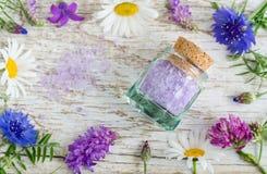 有芳香腌制槽用食盐的小玻璃瓶子与花萃取物 免版税库存图片