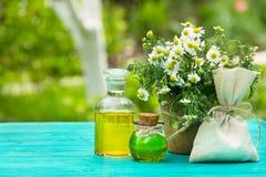 有芳香花卉油和一束的小瓶春黄菊 根本春黄菊油 免版税图库摄影