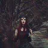 有苍白皮肤和长的红色头发的一名美丽的妇女在一件黑礼服和在黑crownk 有吸血鬼的女孩巫婆 免版税库存照片