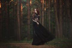有苍白皮肤和非常长的红色头发的一位美丽的哥特式公主在一个黑冠和一件黑长的礼服在一个有薄雾的神仙的森林里 免版税库存图片