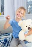 有苍白面孔微笑的病的小女孩坐长沙发 库存图片