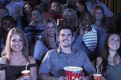 有苏打和玉米花观看的电影的人们在剧院 库存照片