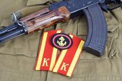 有苏联军队军校学生肩章和苏维埃军队海军陆战队员肩章的AK-47在卡其色的一致的背景 免版税库存照片