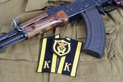 有苏联军队军校学生肩章和苏维埃军队运输军团肩章的AK-47在卡其色的制服 免版税库存照片