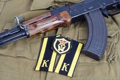 有苏联军队军校学生肩章和苏维埃军队运输军团肩章的AK-47在卡其色的制服 免版税库存图片