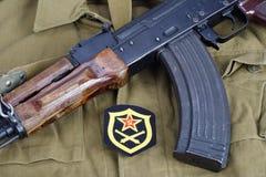 有苏联军队火炮肩章的AK-47在卡其色的一致的背景 库存照片