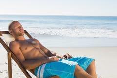 有英俊的人休息,当晒日光浴在他的轻便折叠躺椅时 免版税库存照片