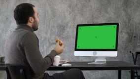 有英俊的商人吃和与某人的电视电话会议 绿色屏幕大模型显示 影视素材
