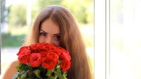 有英国兰开斯特家族族徽花束的少妇在一个开窗口附近的 一个美丽的女孩享受花芳香  股票视频