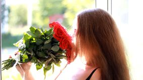 有英国兰开斯特家族族徽花束的少妇在一个开窗口附近的 一个美丽的女孩享受花芳香  影视素材