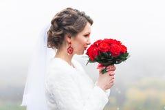 有英国兰开斯特家族族徽花束的年轻可爱的新娘在多雪的圣诞节背景的 免版税库存照片