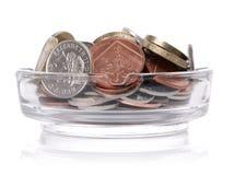 有英国货币的烟灰缸 免版税库存图片
