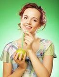 有苹果和秸杆鸡尾酒的愉快的微笑的妇女 免版税库存照片