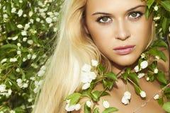 有苹果树的美丽的白肤金发的妇女。夏天 免版税库存图片