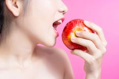 有苹果概念的亚裔妇女 微笑和拿着苹果的她 秀丽面孔和自然构成 隔绝在桃红色背景 免版税库存图片