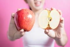 有苹果概念的亚裔妇女 微笑和拿着苹果的她 秀丽面孔和自然构成 隔绝在桃红色背景 图库摄影