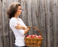 有苹果篮子的成熟妇女  免版税库存照片