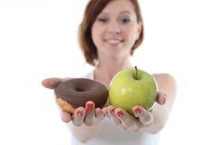 有苹果计算机和巧克力多福饼的妇女在手上 免版税库存图片