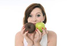 有苹果计算机和巧克力多福饼的妇女在手上 图库摄影
