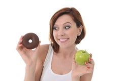 有苹果计算机和巧克力多福饼的妇女在手上 免版税库存照片