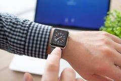 有苹果计算机手表的人在书桌上的手和Macbook 免版税库存照片