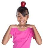 有苹果计算机的女性少年在她顶头II 免版税库存图片