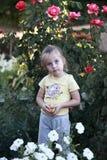有苹果计算机的小女孩在花中 免版税图库摄影