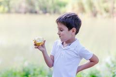 有苹果计算机的男孩在河的河岸 库存图片