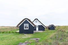 有茅屋顶和木黑门面的传统房子 免版税库存照片
