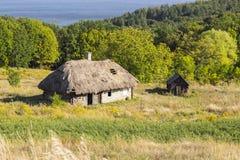 有茅屋顶的在夏天晴天,古老大厦老木屋 库存图片