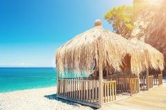 有茅屋顶的机盖在海滩在凯梅尔,土耳其 免版税库存照片