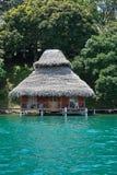 有茅屋顶的热带平房在水 库存图片