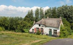 有茅屋顶的老被放弃的农厂房子 库存照片