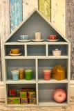 有茶具和立方体的孩子减速火箭的木房子碗柜 免版税库存照片