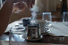 有茶包的小金属茶壶,在餐馆桌上的一些玻璃 白色蒸汽在面汤上上升 r 免版税库存照片