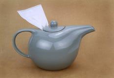 有茶包的茶壶在棕色背景 免版税库存照片