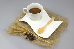 有茶匙的咖啡杯在粗麻布纺织品孤立背景 库存照片
