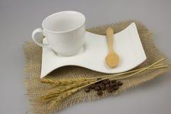 有茶匙的咖啡杯在粗麻布纺织品 免版税库存图片