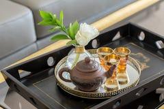 有茶壶和玻璃的木盘子 图库摄影
