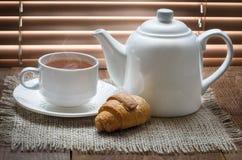 有茶壶的茶杯在老木桌上 免版税库存照片