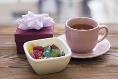 有茶碟、礼物盒和一碗的一个茶杯色的糖果 库存图片